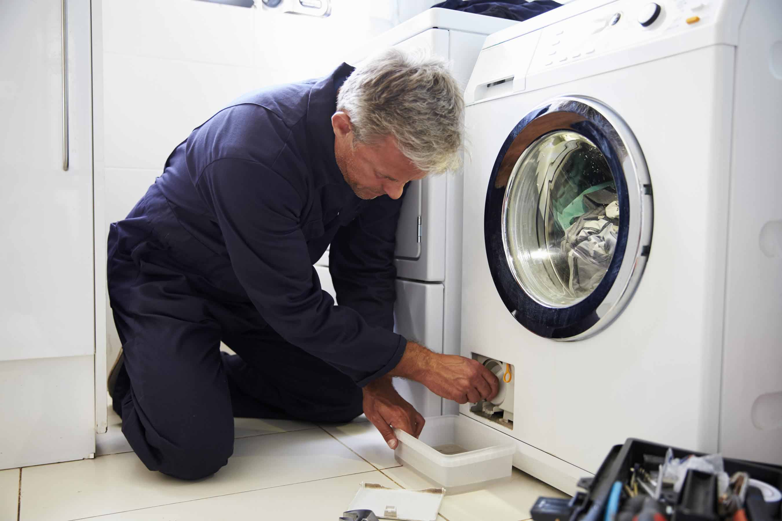 Washing machine technician removing drain filter
